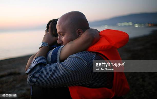 Members of a migrant family from Syria embrace each other after completing a three mile crossing of the Aegean Sea to the island of Kos from Turkey...