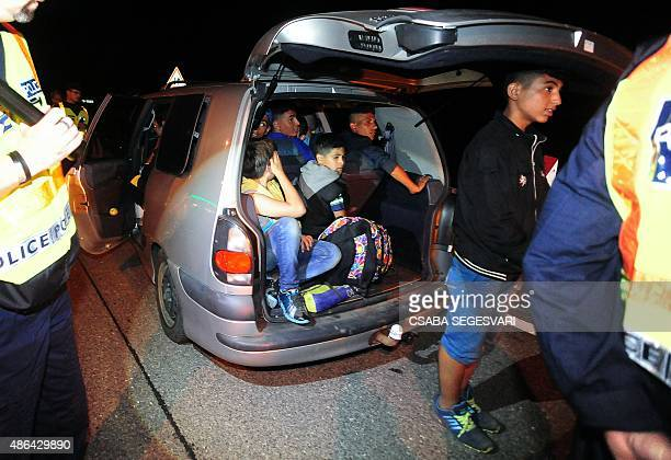 Members of a migrant family sit into a stopped car surrounded by police officers after a suspected smuggler has been arrested by a police officer on...