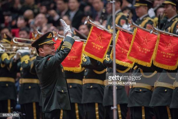 Members of a military band play the national anthem during the fifth plenary session of the first session of the 13th National People's Congress at...