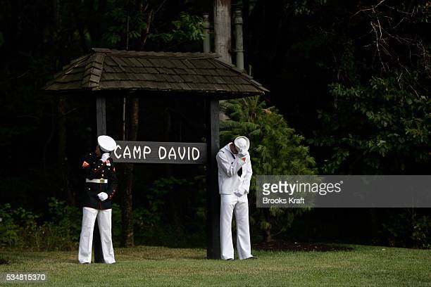 Members of a military honor guard hold their hats as a helocopter carrying British Prime Minister Gordon Brown arrives at Camp David, for meetings...