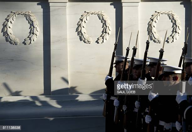 Members of a military honor guard stand alongside the Tomb of the Unknown Soldier at Arlington National Cemetery in Arlington Virginia February 18 as...