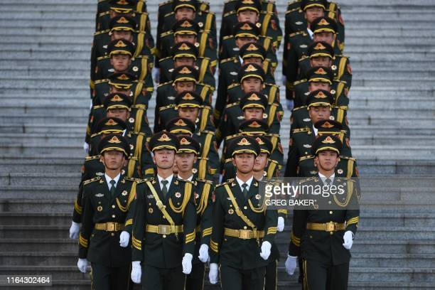 Members of a military honour guard march down the steps of the Great Hall of the People before a welcome ceremony for Uzbekistan's Prime Minister...