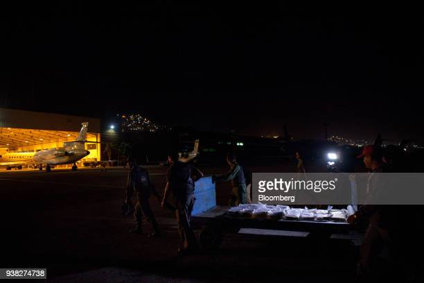 Members of a military transportation agency carry gold bars to an armored vehicle for transport to the Central Bank of Venezuela in Caracas Venezuela...