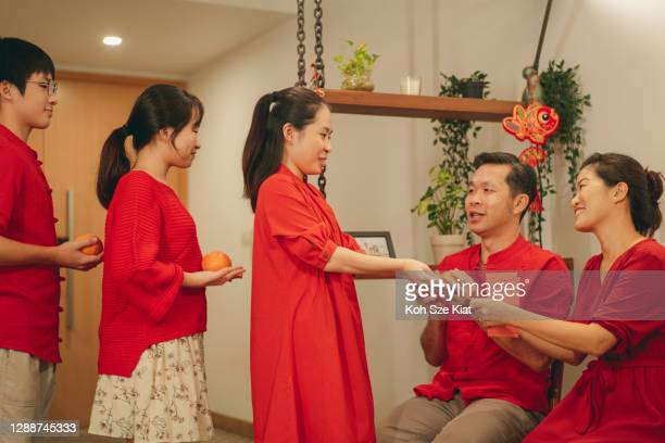 members of a multi generation family exchanging tangerine, red packet and love during chinese new year - new generation stock pictures, royalty-free photos & images