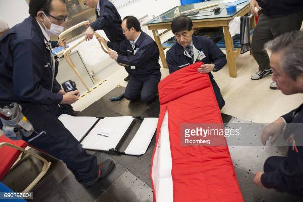Members of a Nitori Holdings Co quality control team take apart a chair to check its components during a product test in Tokyo Japan on Tuesday April...