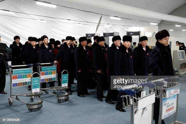 Members of a North Korean delegation of 32 people, including 10 athletes of the North Korean Olympic team, line up to pass through security as they...