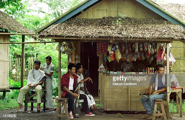 Members of a paramilitary group rest in a store May 2 2000 in a village in Talipao Sulu The group is trying to prevent the escape of members of Abu...