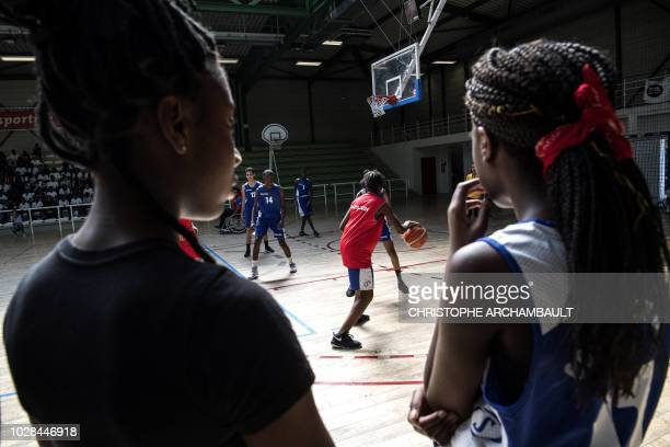 Members of a Paris2024 olympic delegation play basketball with children during a visit by the delegation to a secondary school in the Paris suburb of...