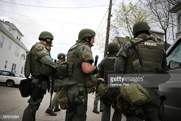 Members of a police SWAT team conduct a door-to-door search for 19-year-old Boston Marathon bombing suspect Dzhokhar A. Tsarnaev on April 19, 2013 in...