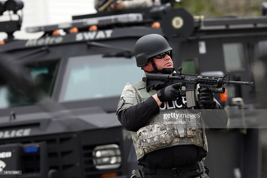 Members of a police S.W.A.T. team search through a neighborhood in Watertown as they search for 19-year-old bombing suspect Dzhokhar A. Tsarnaev on April 19, 2013 in Watertown, Massachusetts. After a car chase and shoot out with police, one suspect in the Boston Marathon bombing, Tamerlan Tsarnaev, 26, was shot and killed by police early morning April 19, and a manhunt is underway for his brother and second suspect, 19-year-old Dzhokhar A. Tsarnaev. The two men are suspects in the bombings at the Boston Marathon on April 15, that killed three people and wounded at least 170.