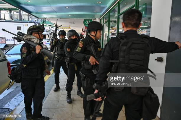 Members of a police SWAT team take positions outside one of the entrances to a mall after a hostage situation was reported in suburban Manila on...