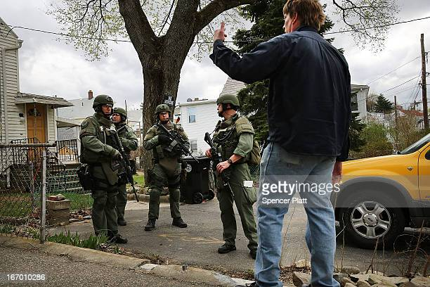Members of a police SWAT team talk to a man while conducting a doortodoor search for 19yearold Boston Marathon bombing suspect Dzhokhar A Tsarnaev on...