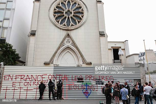 Members of a private security agency stand in front of a barrier with an inscription which translates as 'In France priests are killed and churchs...