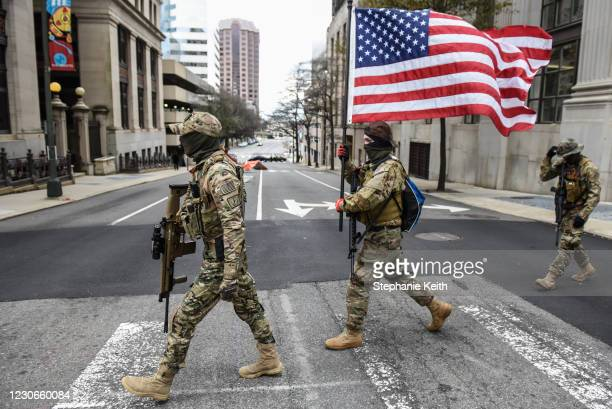 Members of a pro-gun group carry their weapons near the state Capitol on January 18, 2021 in Richmond, Virginia. Capitol Square in Richmond has been...