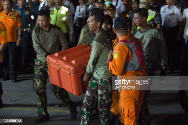 Members of a rescue team carry the flight data recorder part of the illfated Lion Air flight JT 610's black box after it was recovered from the Java...