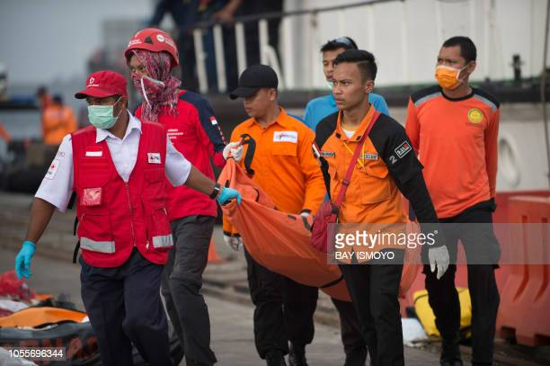 Members of a rescue team carry the remains of victims from the illfated Lion Air flight JT 610 recovered during search operations as they arrive at a...