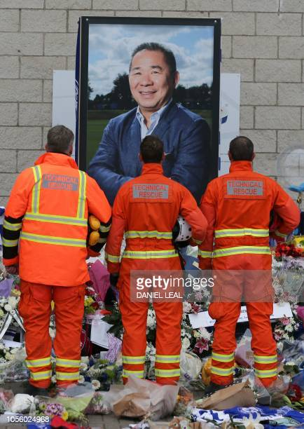 Members of a rescue team pay their respects in front of a portrait of Leicester City Football Club's Thai chairman Vichai Srivaddhanaprabha among the...