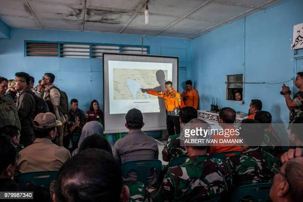Members of a rescue team project a map showing the search and rescue activities of a ferry that capsized on June 18 at Lake Toba ferry port in the...
