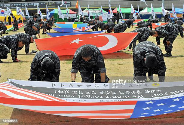 Members of a rightwing association of former special military commandos bow to flags of the 16member UN forces during a ceremony to mark the 58th...