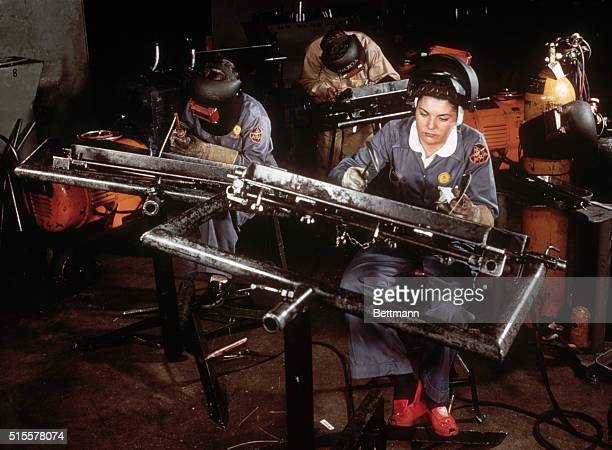 Members of a riveting team at a Vultee Aircraft Corporation aircraft factory use rivet guns and bucking bars to work on a basis trainer plane wing...