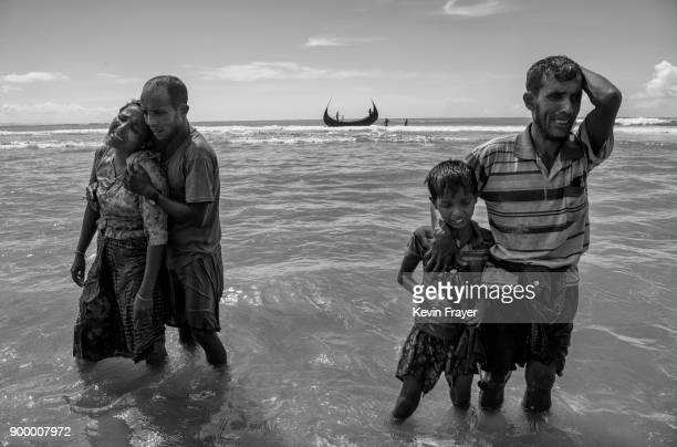 COX'S BAZAR BANGLADESH OCTOBER 01 Members of a Rohingya refugee family cry and react after arriving by boat to Bangladesh side of the Naf River at...