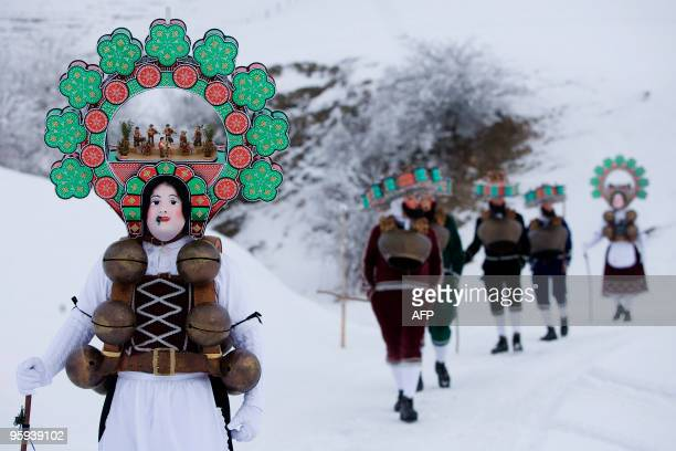 Members of a 'Schuppel' walk in the snow early in the morning as a 'Rolli' is pictured during the 'Silvesterchalusen' in Urnaesch in the Swiss canton...