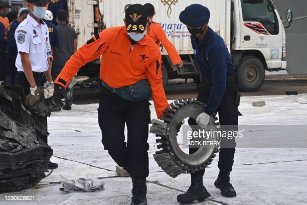 Members of a search and rescue team carry a piece of wreckage from Sriwijaya Air flight SJ182 at Tanjung Priok port, north of Jakarta, on January 11...