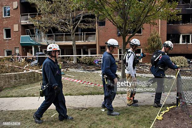Members of a search and rescue team walk past after an explosion at Flower Branch Apartments August 11 2016 in Silver Spring Maryland / AFP / Brendan...