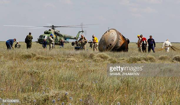 Members of a search and rescue team work at the site of landing of the Soyuz TMA19M capsule carrying International Space Station crew members Tim...
