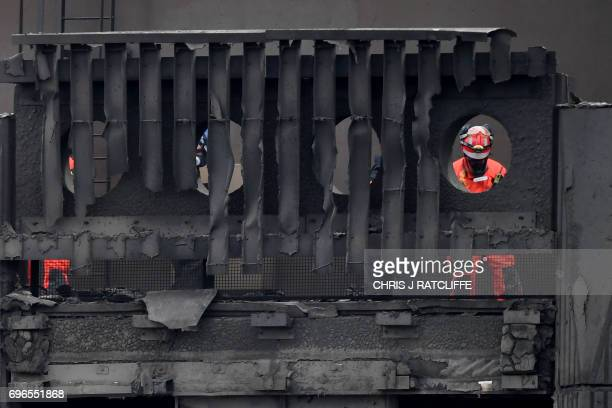 Members of a search and rescue team work near the top of the gutted Grenfell Tower which was ravaged by fire in west London on June 16 2017 The toll...
