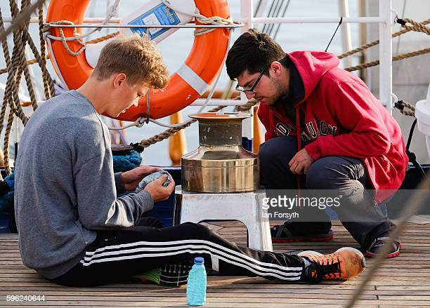 Members of a ships crew polishes brasswork on deck during the North Sea Tall Ships Regatta on August 27 2016 in Blyth England The bustling port town...