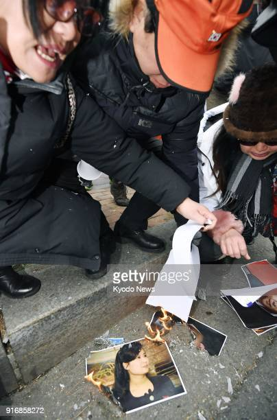 Members of a South Korean conservative group burn a photograph of Hyon Song Wol leader of North Korea's Samjiyon Orchestra during a rally in Seoul on...