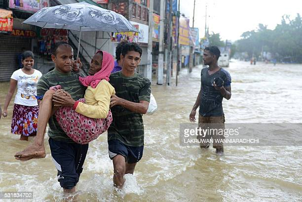 Members of a Sri Lankan Army rescue team carry a woman to safety through floodwaters in the suburb of Kaduwela in capital Colombo on May 17 2016...