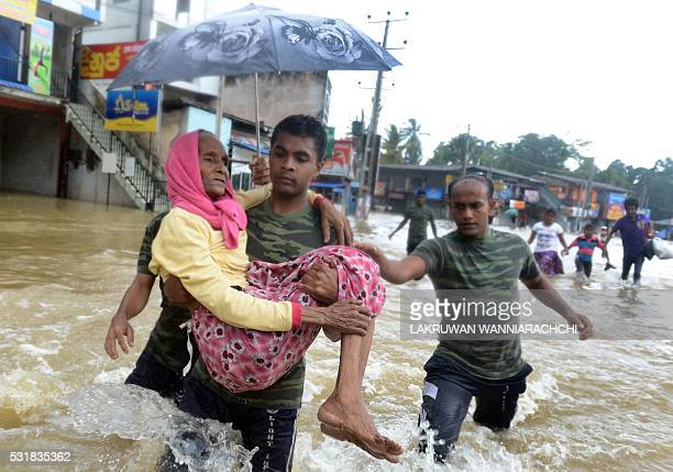 TOPSHOT Members of a Sri Lankan Army rescue team carry a woman to safety through floodwaters in the suburb of Kaduwela in capital Colombo on May 17...