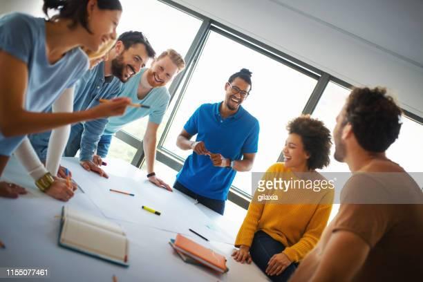 membros de uma empresa de design de inicialização em uma reunião. - mesa de reunião - fotografias e filmes do acervo