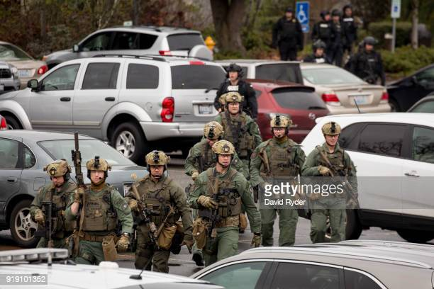 Members of a SWAT team walk through a parking lot after a threat of an active shooter shut down campus at Highline College on February 16 2018 in Des...