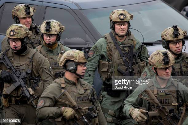 Members of a SWAT team walk through a parking lot after a threat of an active shooter shut down campus at Highline College on February 16, 2018 in...