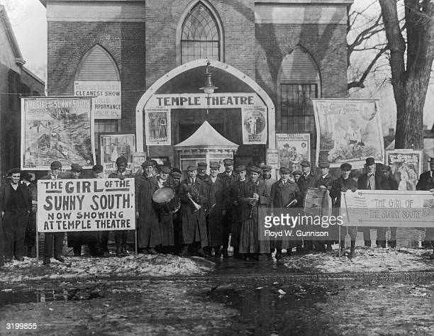 Members of a symphony band stand among banners and posters for the silent film 'The Girl of the Sunny South' as they pose in front of the Temple...