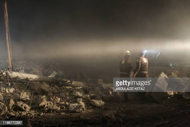 Members of a Syrian civil defence team known as the White Helmets search for survivors under the rubble of a building following reported airstrikes...