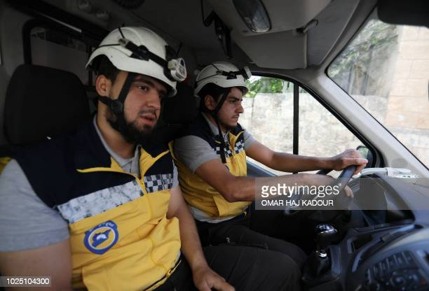 Members of a Syrian civil defence team known as The White Helmets sit in an ambulance after receiving an alert in the rebelheld northern Syrian city...