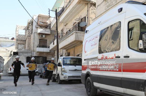 Members of a Syrian civil defence team known as The White Helmets rush to an ambulance after receiving an alert in the rebelheld northern Syrian city...