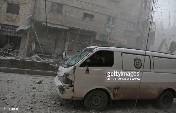 Members of a Syrian civil defence team known as White Helmets drive their vehicle during a rescue operation following a reported regime air strike in...