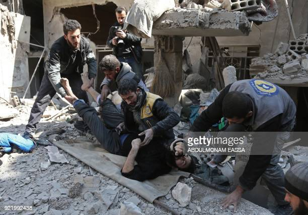 Members of a Syrian civil defence team rescue a man following a reported regime air strike in the rebelheld town of Hamouria in the besieged Eastern...