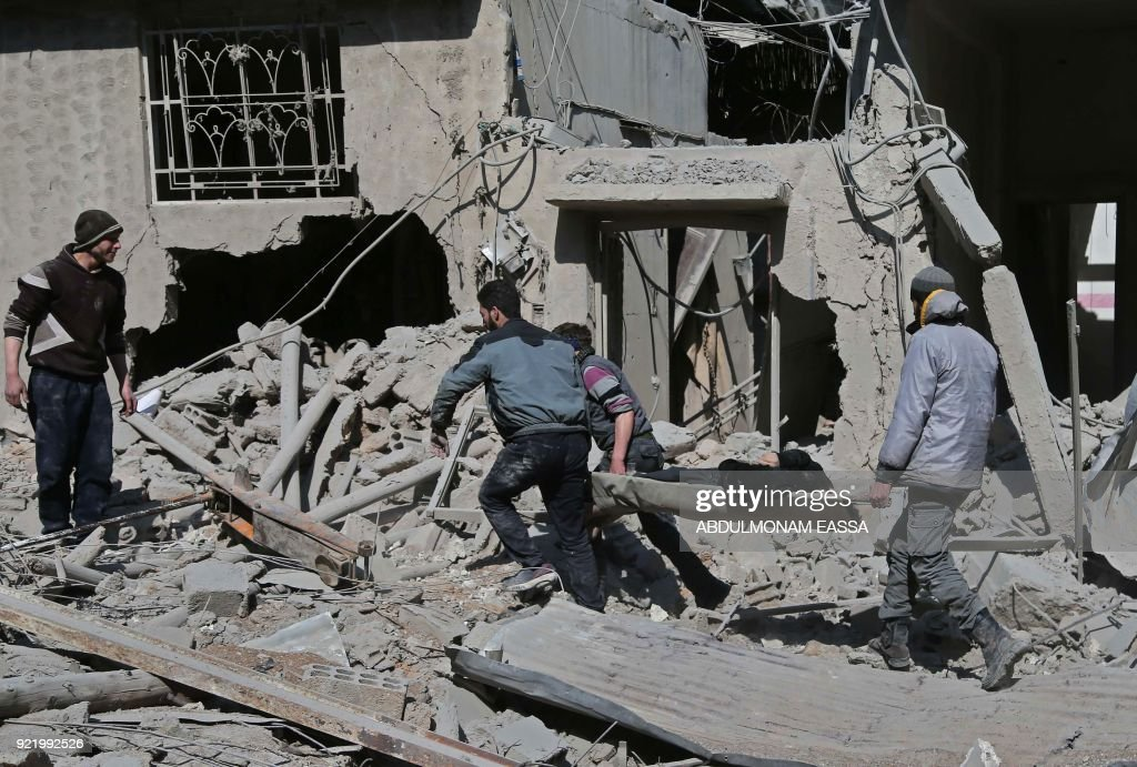 Members of a Syrian civil defence team rescue a man following a reported regime air strike in the rebel-held town of Hamouria, in the besieged Eastern Ghouta region on the outskirts of the capital Damascus on February 21, 2018. /