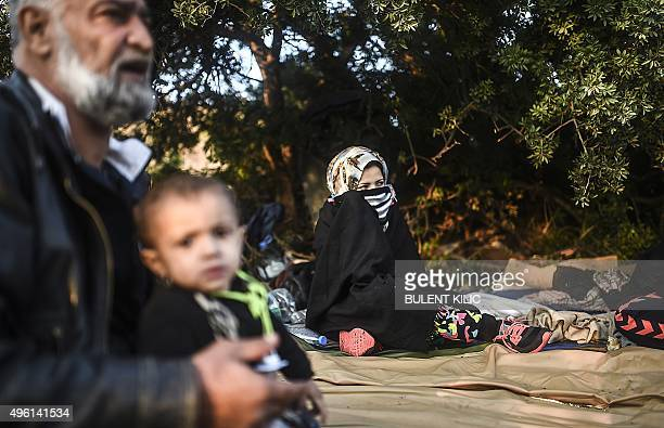 Members of a Syrian family hide behind bushes as migrants and refugees wait for the night to fall to try to cross to the Greek island of Kos from...