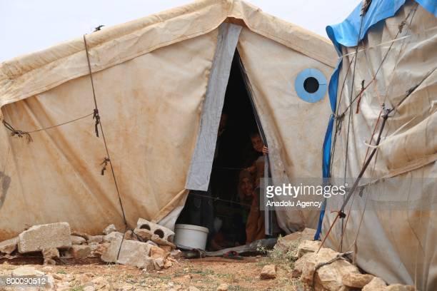 Members of a Syrian family peek through their tent during Muslim's holy month of Ramadan in Idlib Syria on June 23 2017 Ahead of Eid al Fitr Syrian...