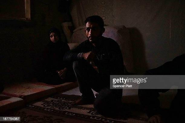 Members of a Syrian family sit inside of a room in a half finished house they are sharing with dozens of other refugees only miles from the border...