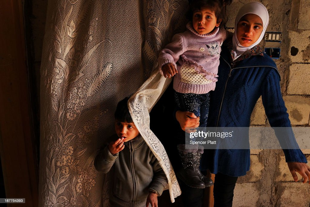 Members of a Syrian family stand in the door way of a half finished house they are sharing with dozens of other refugees only miles from the border with Syria in the Bekaa Valley on November 12, 2013 in Majdal Anjar, Lebanon. As the war in neighboring Syria drags on for a third year, Lebanon, a country of only 4 million people, is now home to the largest number of Syrian refugees who have fled the conflict. The situation is beginning to put huge social and political strains on Lebanon as there is currently no end in sight to the war in Syria.