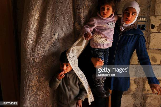 Members of a Syrian family stand in the door way of a half finished house they are sharing with dozens of other refugees only miles from the border...