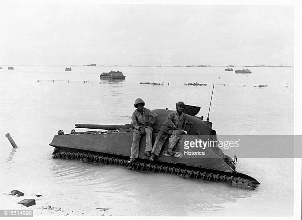 Members of a tank unit sit atop their giant vehicle which is stalled in a waterfilled shell hole on Tarawa Other immobilized armored amphibious...